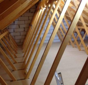 Inside loft with flooring and trusses
